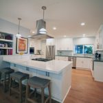 A kitchen featuring a peninsula, LED recessed lighting, pendant lighting, and shake style cabinetry.