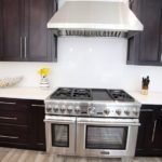 Wall showing dark wood shaker style cabinets, white countertops, white solid stone backsplash and light wood flooring